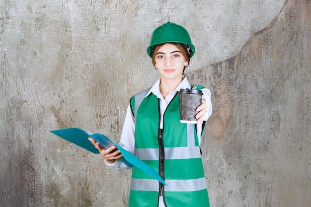 Engenheira de uniforme verde e capacete, segurando uma pasta de projeto verde e compartilhando um copo de bebida com seu colega.
