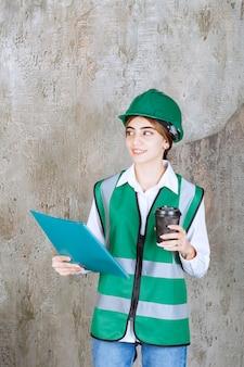 Engenheira de uniforme verde e capacete segurando uma pasta de projeto verde e um copo de bebida.