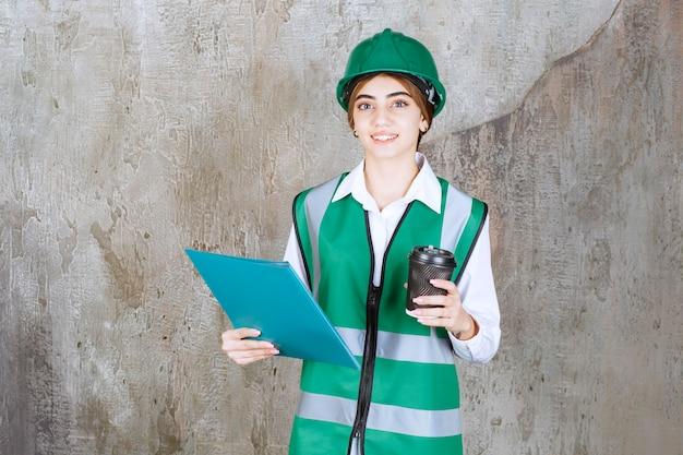 Engenheira de uniforme verde e capacete segurando uma pasta de projeto verde e um copo de bebida