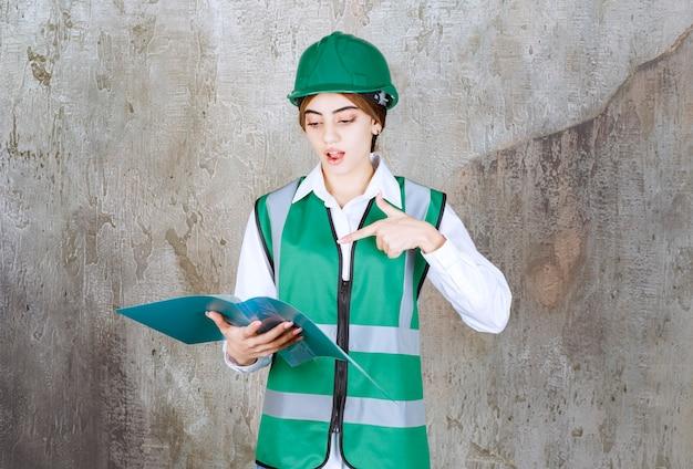 Engenheira de uniforme verde e capacete segurando uma pasta de projeto verde, lendo e fazendo comentários.