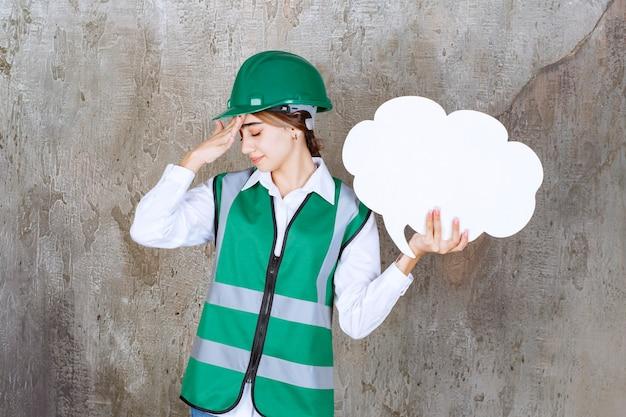 Engenheira de uniforme verde e capacete segurando uma placa de informações de forma de nuvem e parece cansada e com sono.