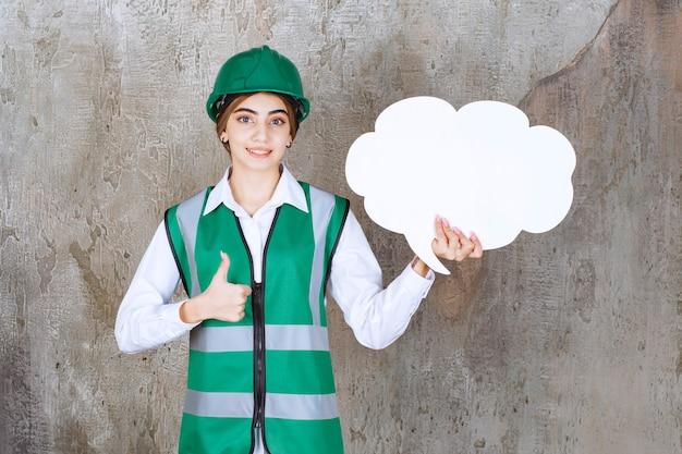 Engenheira de uniforme verde e capacete segurando uma placa de informações em forma de nuvem e mostrando sinal com a mão positiva