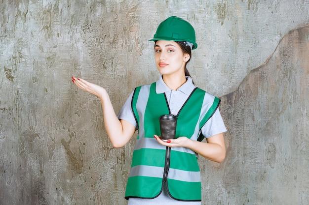 Engenheira de uniforme verde e capacete segurando uma xícara de café preto e mostrando algo à parte.