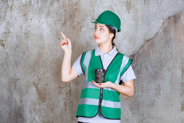 Engenheira de uniforme verde e capacete segurando uma xícara de café preto e mostrando algo à parte