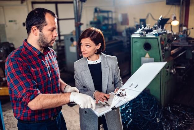 Engenheira discutindo com o mecânico segurando a roda dentada e analisando a planta