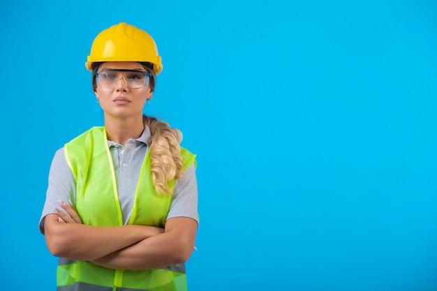 Engenheira em capacete amarelo e engrenagem usando óculos preventivos.