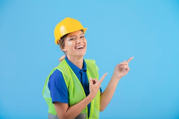 Engenheira em capacete amarelo e equipamento apresentando algo.