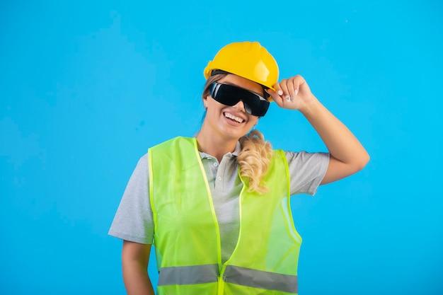 Engenheira em capacete amarelo e equipamento usando óculos preventivos de raio e sentimento positivo.