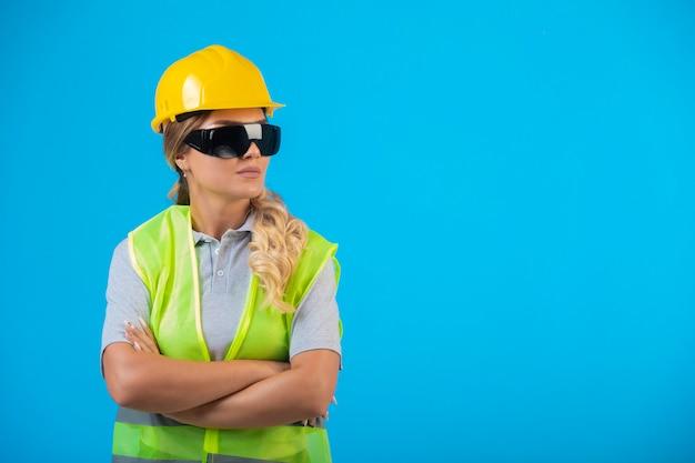 Engenheira em capacete amarelo e equipamento usando óculos preventivos de raio se passando por um profissional.