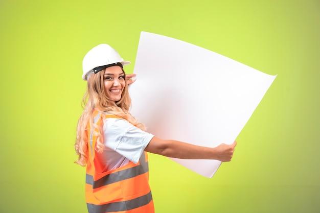 Engenheira em capacete branco e engrenagem segurando o plano de projeto.