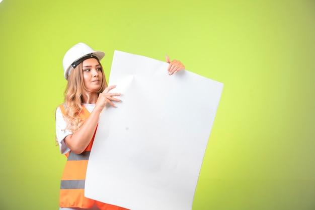 Engenheira em capacete branco e equipamento mostrando o plano de construção.