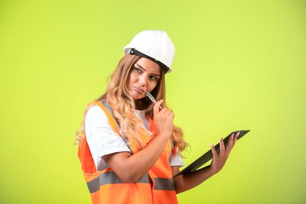 Engenheira em capacete branco e equipamento segurando a lista de verificação e pensamento.