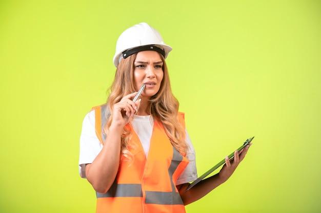 Engenheira em capacete branco e equipamento segurando a lista de verificação e sente-se em dúvida.