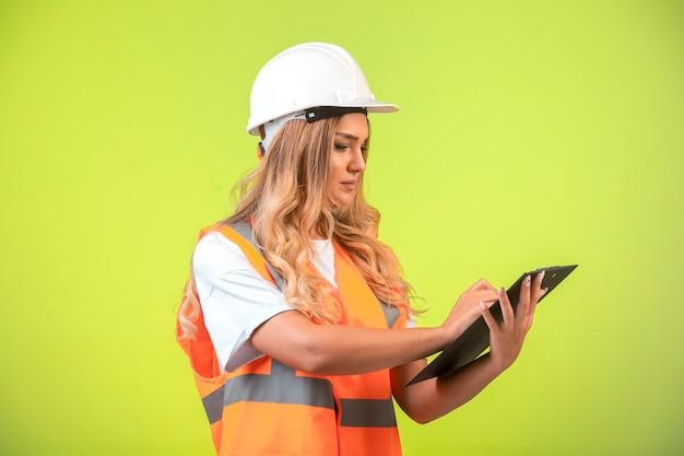 Engenheira em capacete branco e equipamento segurando a lista de verificação e tomando notas.