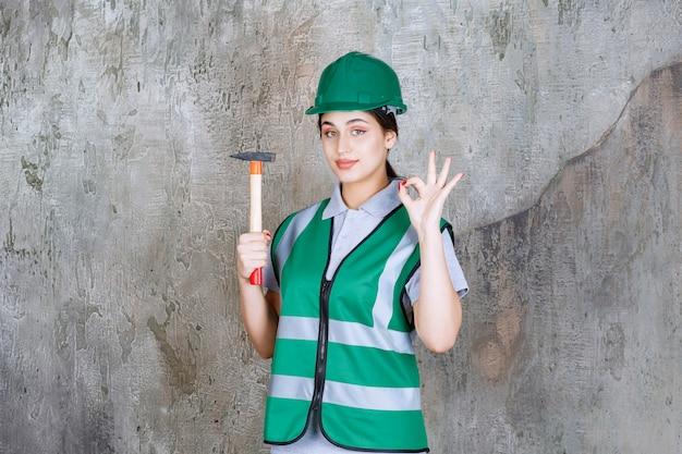 Engenheira em capacete verde, segurando um machado de madeira para uma obra de reparação e mostrando sinal de mão positivo.