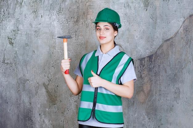 Engenheira em capacete verde, segurando um machado de madeira para uma obra de reparação e mostrando sinal positivo com a mão.