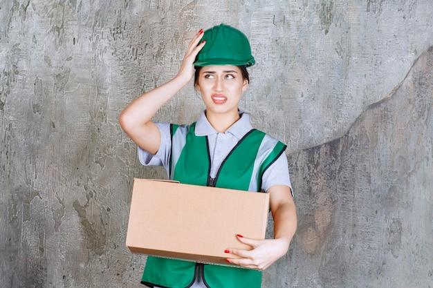 Engenheira em capacete verde segurando uma caixa de papelão e parece confusa e apavorada.