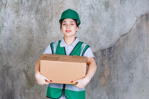 Engenheira em capacete verde segurando uma caixa de papelão.
