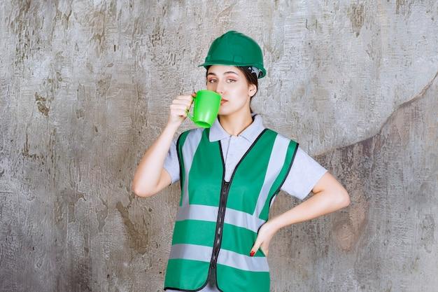 Engenheira em capacete verde, segurando uma caneca de café verde e bebendo.