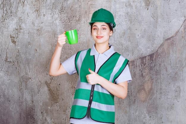Engenheira em capacete verde, segurando uma caneca de café verde e mostrando sinal de prazer.