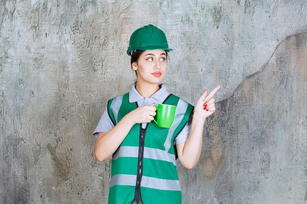 Engenheira em capacete verde, segurando uma caneca de café verde.
