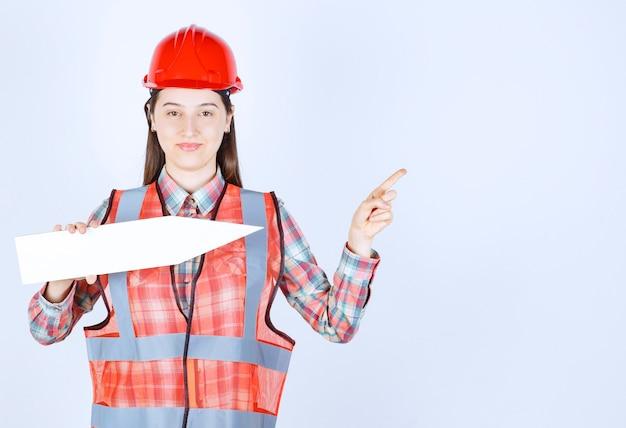 Engenheira em capacete vermelho, segurando uma seta apontando para a direita.