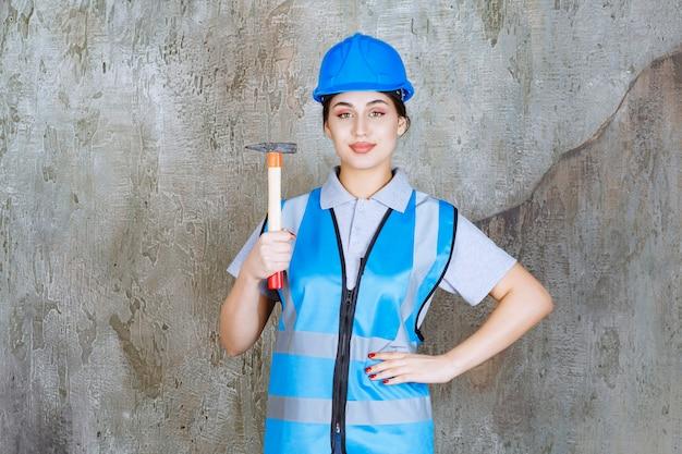 Engenheira em engrenagem azul e capacete segurando um machado com cabo de madeira.