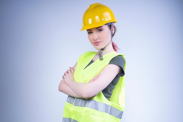 Engenheira linda em um capacete amarelo cruzou os braços