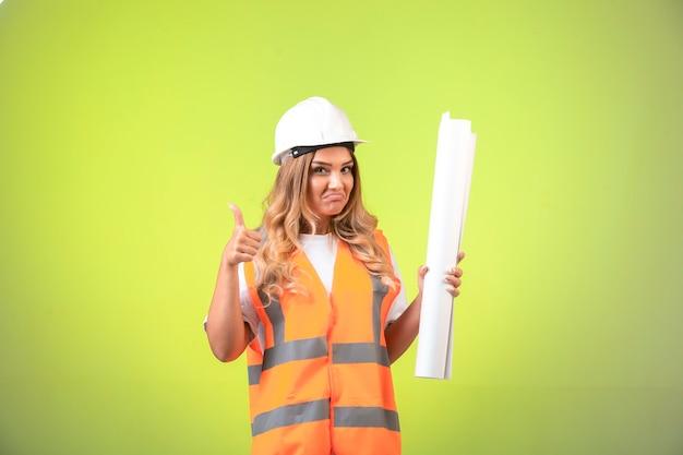 Engenheira no capacete e equipamento segurando o plano de construção e compõe o polegar.