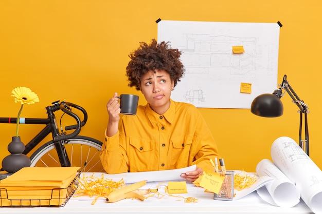 Engenheira profissional habilidosa bebe café prepara desenhos para o projeto de desenvolvimento da casa, mergulhando em pensamentos, poses na área de trabalho com papéis ao redor