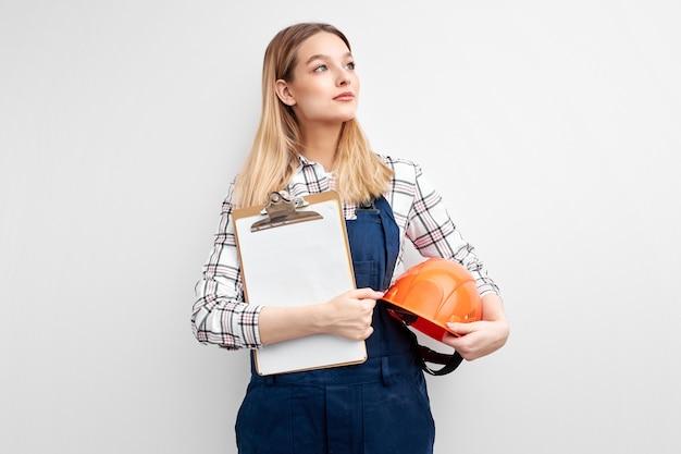 Engenheira segurando um tablet de papel e um capacete, vestida com uniforme de construtor