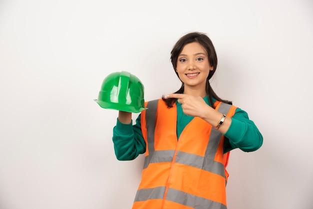 Engenheira sorridente segurando um capacete em fundo branco.