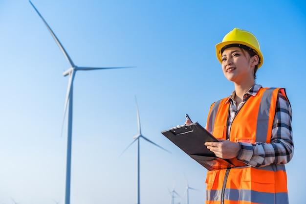 Engenheira trabalhando e escrevendo em uma prancheta contra uma fazenda de turbinas eólicas