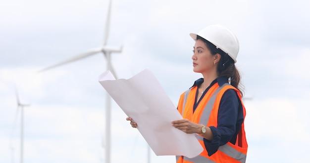 Engenheira trabalhando no local em uma fazenda de turbinas eólicas