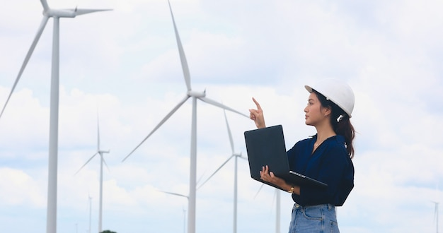 Engenheira usando tablet para trabalhar no local em uma fazenda de turbinas eólicas