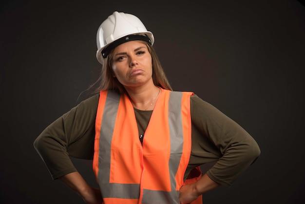 Engenheira usando um capacete branco e equipamento e parece confiante.