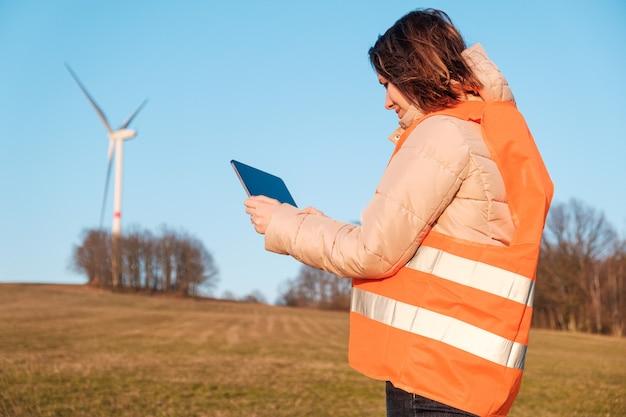 Engenheira verificando ou consertando moinhos ou turbinas eólicas usando um tablet em uma vesta laranja