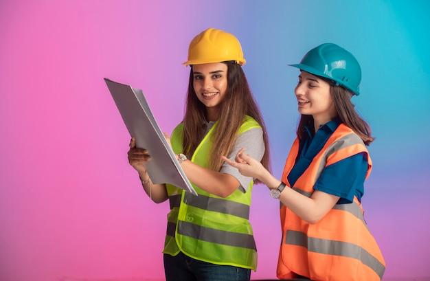 Engenheiras de construção trabalhando juntas e discutindo o plano do projeto