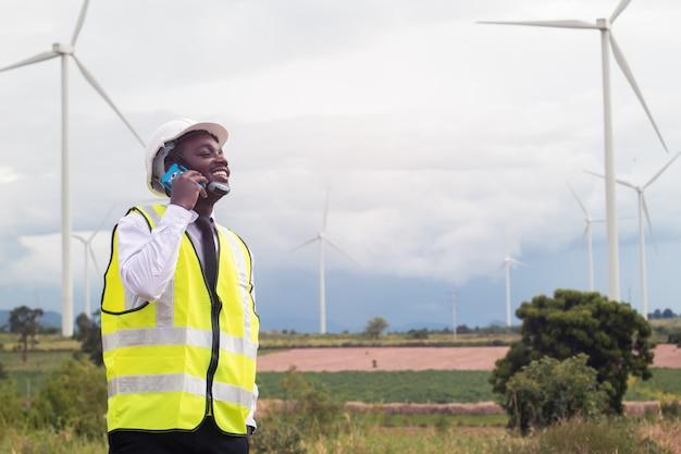 Engenheiro africano em pé e falando smartphone com turbina eólica