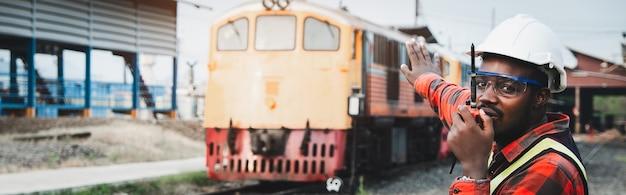 Engenheiro africano levantou a mão para controlar um trem na ferrovia falando por comunicação de rádio ou walkie talkie