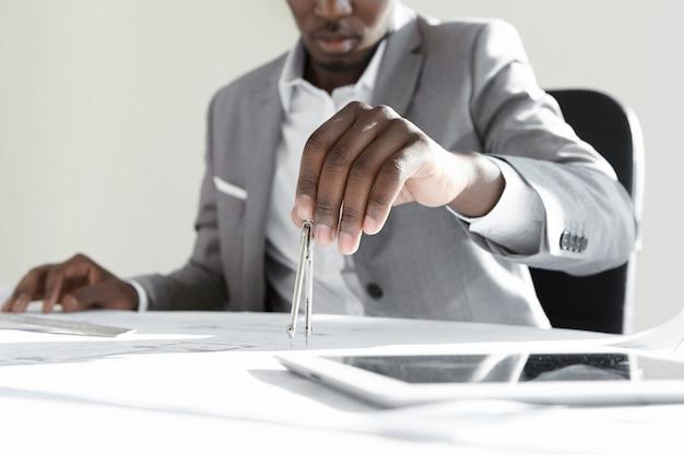 Engenheiro africano usando ferramenta de desenho técnico para calcular medidas