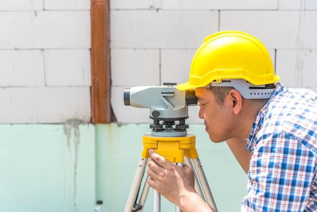 Engenheiro agrimensor profissional ou arquiteto trabalhando e medindo o nível na construção si