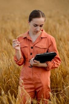 Engenheiro agrônomo de mulher caucasiana com computador tablet no campo de trigo, verificando a qualidade e o crescimento das safras para a agricultura. agricultura e conceito de colheita.