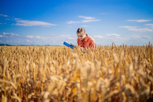 Engenheiro agrônomo de mulher caucasiana com computador tablet no campo de trigo, verificando a qualidade