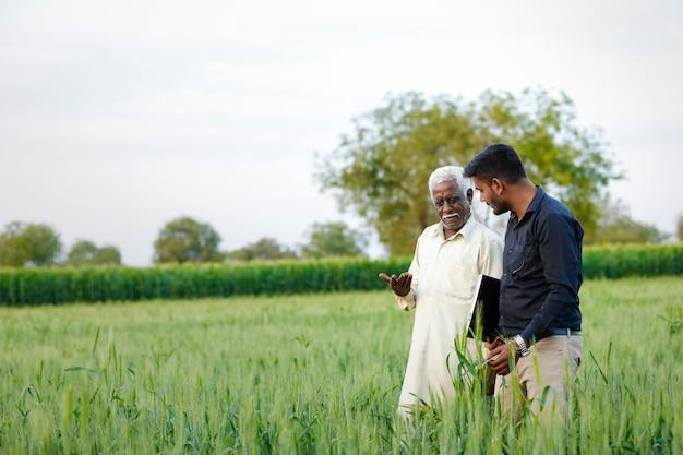 Engenheiro agrônomo indiano novo com o fazendeiro no campo
