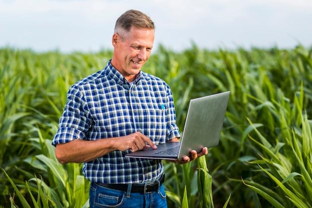 Engenheiro agrônomo sorridente usando um laptop