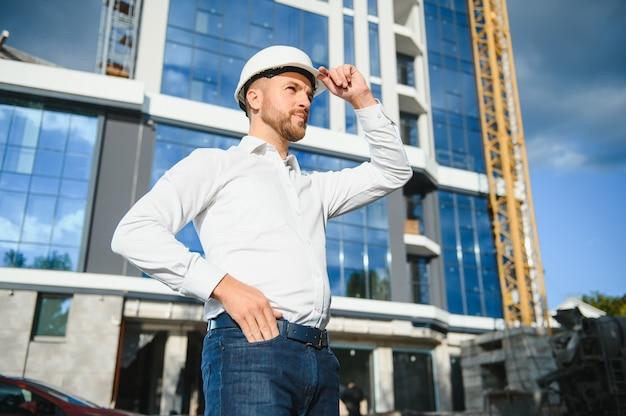 Engenheiro ao lado de guindastes de construção. conceito - grande projeto de construção. o arquiteto dirige o processo de construção. desenhos e tablet nas mãos.