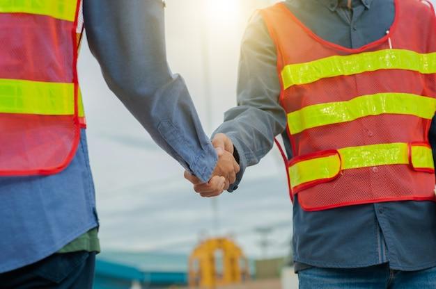 Engenheiro aperta a mão equipe engenheiro faz o trabalho na construção do local, arquitetura do trabalho em equipe, equipe aperta a mão