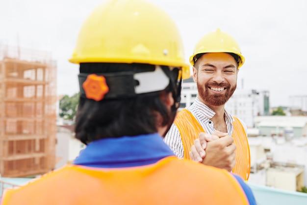 Engenheiro apertando a mão do empreiteiro