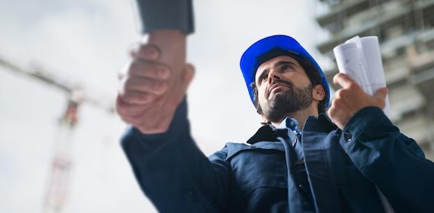 Engenheiro, apertando as mãos com um cliente